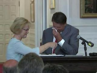 Health and Human Services Secretary Aldona Wos hands Gov. Pat McCrory a tissue during an Aug. 5, 2015, news conference to announce her resignation. New DHHS Secretary Rick Brajer looks on.