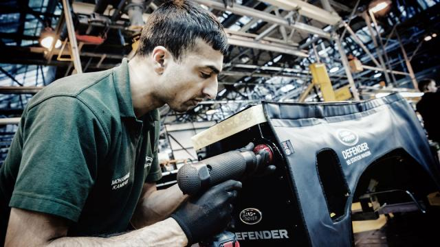 An worker assembles the Land Rover Defender at the auto manufacturer's production line at Solihull, England (Image courtesy of Land Rover