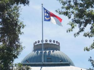 The North Carolina flag flies over the historic state capitol building.