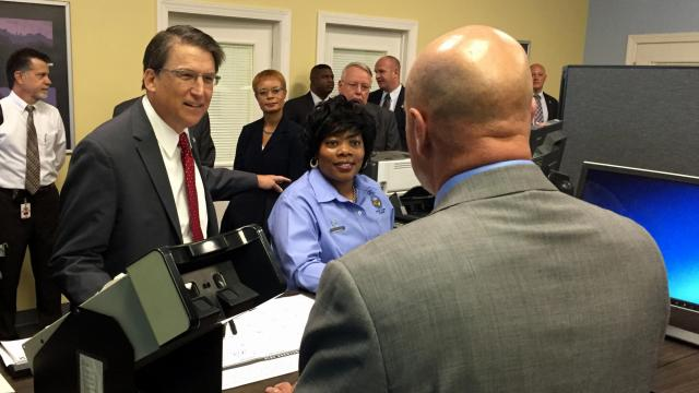 Gov. Pat McCrory listens on 10/12/15 as DMV Commissioner  Kelly Thomas explains new procedures used at DMV offices to improve customer service.