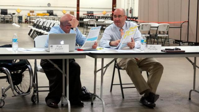 Wake County Board of Elections members Mark Ezzell and Brian Ratledge discuss provisional ballots during the Wake County Board of Elections canvass meeting on March 24, 2016.