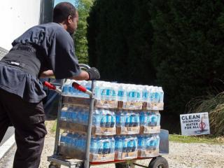 A Duke Energy contractor delivers bottled water to a home on Leonard Road in Salisbury, N.C., near the Buck steam plant on April 7, 2016 (Tyler Dukes/WRAL).