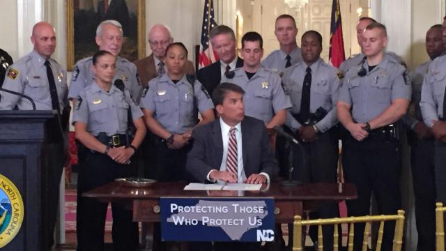 "Gov. Pat McCrory was flanked by law enforcement officers as he signed a measure that created the ""blue alert"" system."
