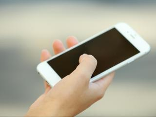 A female hand holding a mobile phone outdoors, on blurred backgr