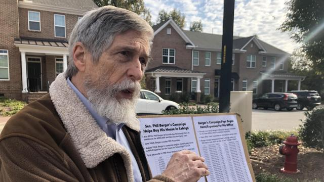 Campaign finance watchdog Bob Hall outside a townhouse owned by Senate Leader Phil Berger, questioning Berger's use of campaign funds to pay for the Raleigh home.
