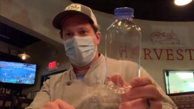Jason Smith, owner of 18 Restaurant Group in Raleigh, shows off a sealed container that restaurants and bars will have to use to sell to-go mixed drinks during the pandemic. WRAL/Aaron Thomas)