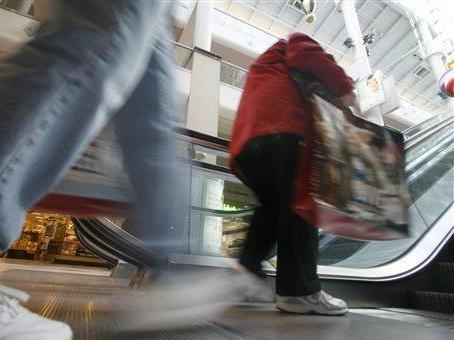 Shoppers carrying shopping bags step onto the escalator at Emerald Square Mall in North Attleboro, Mass., Saturday, Nov. 24, 2007. Stores are counting on hordes of shoppers who have been pulling back in recent months amid a challenging economy to snap up bargains. (AP Photo/Stew Milne)