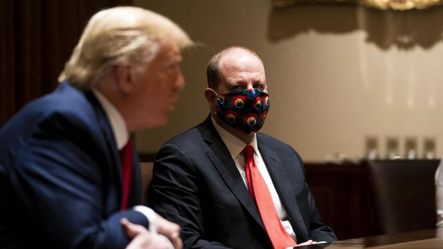 """FILE -- President Donald Trump during a meeting with Colorado Gov. Jared Polis, a Democrat, right, at the White House in Washington, May 13, 2020. """"Refusing to cover one's face is reckless, selfish behavior that imperils the economy and can kill or endanger innocent people,"""" writes Nicholas Kristof. (Doug Mills/The New York Times)"""