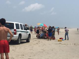 Older man Bitten by shark and taken from beach by end.
