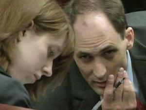 Brad Cooper speaks to a member of his defense team on April 14, 2011, during his first-degree murder trial.