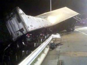 A tractor-trailer goes over a highway guardrail on an I-540 exit ramp to U.S. 64 Business after colliding with a car.