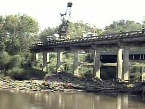 A DOT crane removes logs piled up against the supports for the U.S. 401 bridge over the Cape Fear River in Lillington on Sept. 29, 2008.
