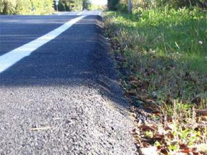 The Safety Edge technique adds a 30 degree slope between the edge of the resurfaced road and the unpaved shoulder.