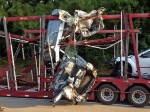 A tractor-trailer carrying new cars on U.S. Highway 64 West hit a train trestle early Wednesday at Laura Duncan Road in Apex, officials said.