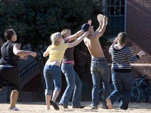 Students on NCSU campus play frisbee on the grass outside Alexander dorm.