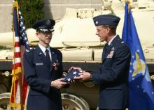 Lt Col Doug Clark (commander OL K, ACC) presents a flag flown over the U.S. Capital.