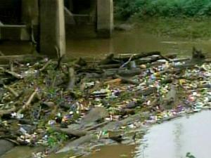 Tires, limbs and trash collect at the base of a bridge.