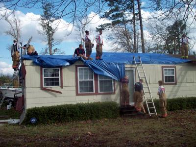 The Sharpsburg Volunteer Fire Department helps put a tarp on the roof of a home on Heffner Road. The home lost its roof during a storm that produced several tornadoes on Nov. 15, 2008.