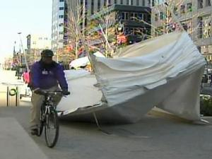 Wind knocks over a tent in downtown Raleigh Wednesday as a bicyclist rides by.