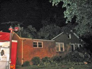 Winds toppled a 2½-foot wide tree that fell on a home at 7190 Siler City Snow Camp Road in Chatham County on Tuesday evening. A family of four that was home at the time escaped unharmed. (Photo courtesy of Mark Gaines/Silk Hope Volunteer Fire Department.)