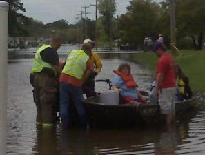 Crews rescue a woman from rising waters in Windsor, in Bertie County. By 2 p.m. Friday, crews had rescued more than 50 people.