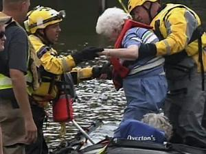 Rescue workers help 91-year-old Louise Pearce out of a raft in Windsor, one of several communities hit hard by rising rivers and creeks.