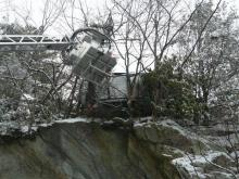 A bucket truck reaches out to an SUV suspended on the side of a Blowing Rock cliff.