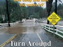 "A flooded roadway with a ""turn around, don't drown"" sign. (Courtesy: NWS)"