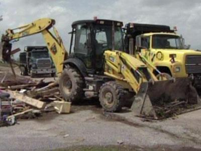 Bulldozers push the remnants of Sherry Baker's Dunn home into a pile on April 27, 2011.