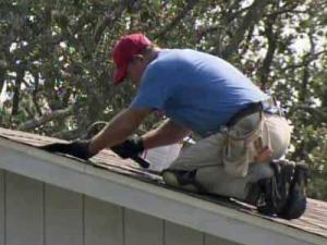 A man repairs a shingle on a roof of a house on Harkers Island on Aug. 29, 2011.
