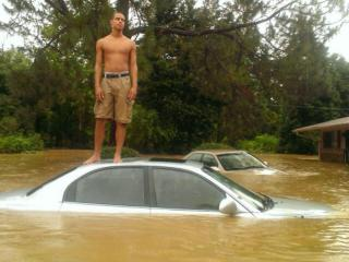 A Camelot Village resident stands on top of his car after flood waters sweep Chapel Hill.