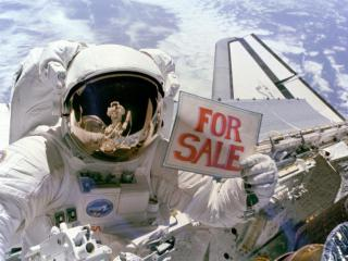 Astronaut Dale A. Gardner holds up a For Sale sign after retrieving a pair of satellites during Space Shuttle mission STS-51-A. (Photo credit: NASA)