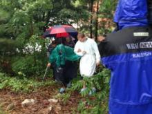 In Raleigh, flooding blocked the entrance to a dialysis clinic, preventing ambulances from getting to patients. Some of the patients had to walk up a rocky hill through the woods to get to the waiting ambulances. (Photo by Sloane Heffernan/WRAL)