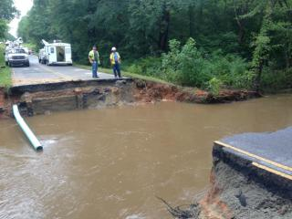 A heavy downpour caused a 25-foot section of Airport Road in Warrenton to collapse early Monday, Sept. 9, 2014, causing two cars and an underground pipe to be swept away by raging flood waters.