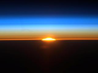 Astronauts see similar colors of sunlight refracted through the atmosphere during sunrises viewed from the International Space Station as those seen by Apollo 12 astronauts during their eclipse viewing in 1968.
