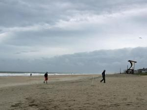 A handful of beach-goers stroll along Wrightsville Beach early Sunday after Tropical Storm Ana made landfall near Myrtle Beach, S.C.