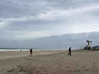 A handful of beach-goers stroll along Wrightsville Beach early Sunday after Tropical Storm Ana made landfall near Myrtle Beach, S.C.