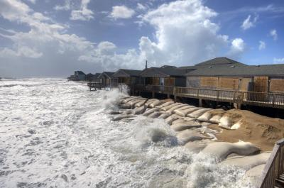Days of heavy rain and the passing offshore of Hurricane Joaquin pushed waves and sand onto roads in Buxton. (Photos by Donny Bowers)
