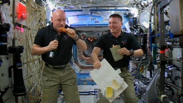 Astronaut Scott Kelly samples candied yams from a pouch as Kjell Lindgren looks on with smoked turkey (Credit: NASA/JSC)