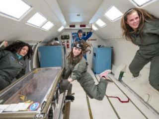 UNC-Pembroke student Molly Musselwhite works with the team's experiments in the glove box while Georgianna Revels, right, floats on the wall. during a 2014 flight (Credit: NASA/UNC-Pembroke)