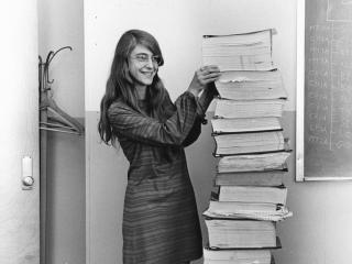 Margaret Hamilton stands next to assembly code listing of the navigation software she and her MIT team created for the Apollo program (Credit: MIT Draper Laboratory)