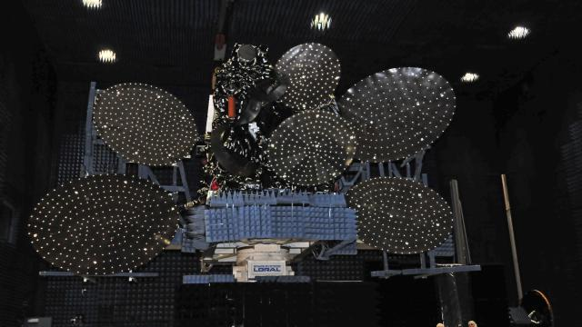You get an appreciation for how large communications satellites when standing under them. The blue material absorbs energy during testing. (Credit: SSL)