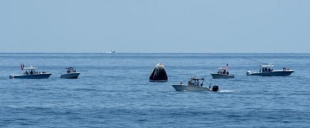 curious recreational boaters arrive at the SpaceX Crew Dragon Endeavour spacecraft shortly after splashdown
