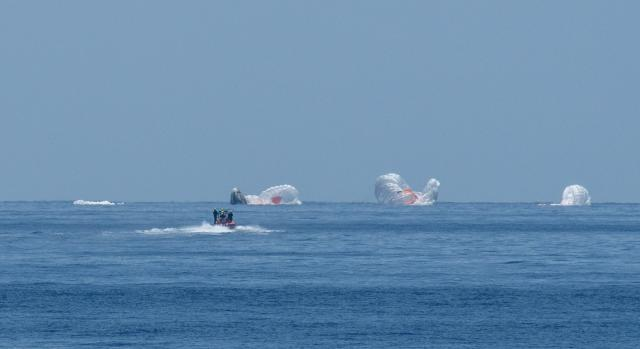 Recovery crews speed to the SpaceX Dragon capsule and four main chutes.