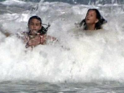 Two girls hit the waves along Kill Devil Hills on Aug. 21, 2009. Swells were expected to reach from 7 to 14 feet in some areas when Hurricane Bill moves past the coast.