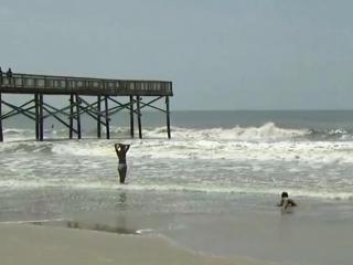 Beach-goers test the waters at Atlantic Beach after Hurricane Arthur cleared the coast Friday, July 4, 2014.