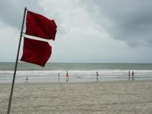 The red hurricane flag flaps in the wind, while families enjoy the ocean at Myrtle Beach before the arrival of Tropical Storm Isaias.