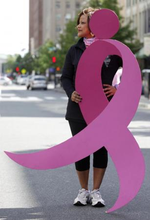 WRAL anchor Pam Saulsby holding Komen's iconic ribbon.