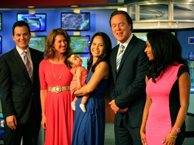 WRAL anchor Renee Chou visits the newsroom with her newborn daughter, Elsa, as traffic reporter Brian Shrader, meteorologist Elizabeth Gardner and anchors Bill Leslie and Michelle Marsh look on.<br/>Photographer: Kelly Hinchcliffe